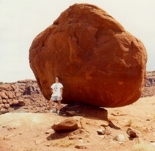 My niece standing in front of a balancing rock in Canyonlands National Park.
