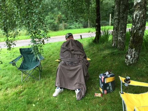 Steve is being harassed by midges and their bites. So has used a blanket to cover himself up. Midges are rampant at this time of year in Scotland.