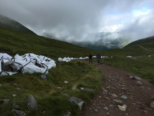 Industrial sacks laden with rocks line the side of the mountain track, these have been brought in by helicopter. The friends of Ben Nevis volunteers will use them to reinforce the track against erosion.