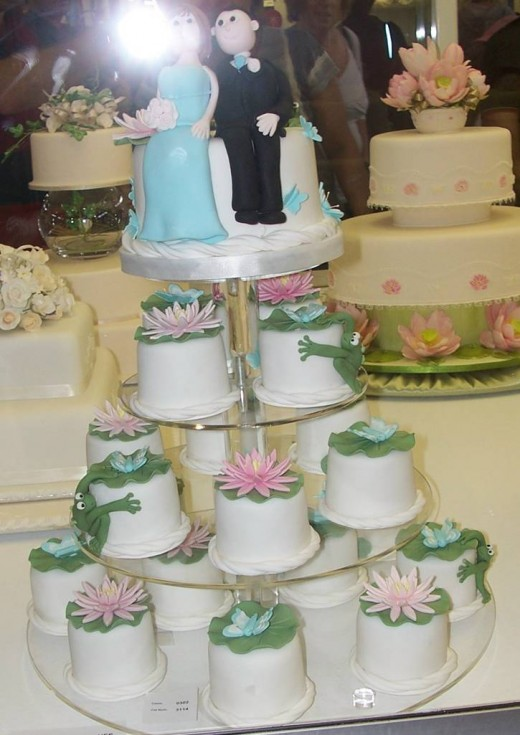An amazing wedding cake that is made of pink water lily, blue butterflies and frogs.