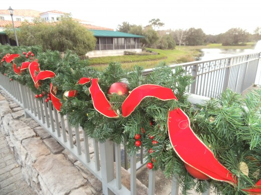 This beautifully decorated bridge railing with garlands, oversized ornaments, and a red with gold ribbon was created by the Disney decorators. Wouldn't this look great on your fence or porch railing!