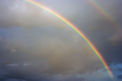 An image of a rainbow over the backdrop of gloomy clouds.