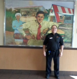 General Manager Tod Seals standing in front of the mural depicting Harmon Dobson, the Founder, and his wife Grace Williamson Dobson in front of the first Whataburger located on Ayers Street in Corpus Christi, Texas.