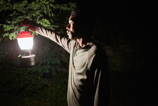 Travis (Kelvin Harrison Jr) holding a  red lantern to get through the dark wilderness.
