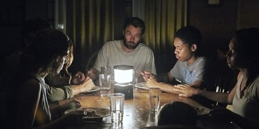 Paul and Will's family eating together in the dark.