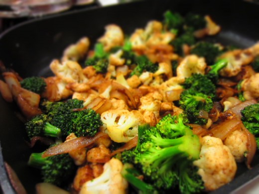 Hat olive oil and add butter to pan. Fry boiled cauliflower and broccoli pieces.
