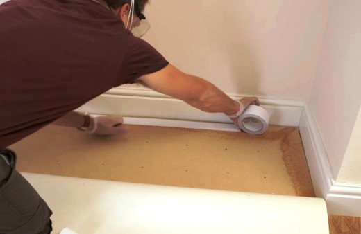 Stick the tape to the floor around the edges of the room without removing the backing paper.
