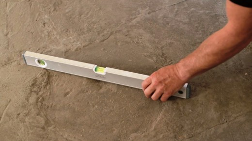 Check how deep any holes or dips are by placing a spirit level across the floor area.