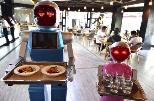 Robots working as waiters and waitresses, serving food and drinks.