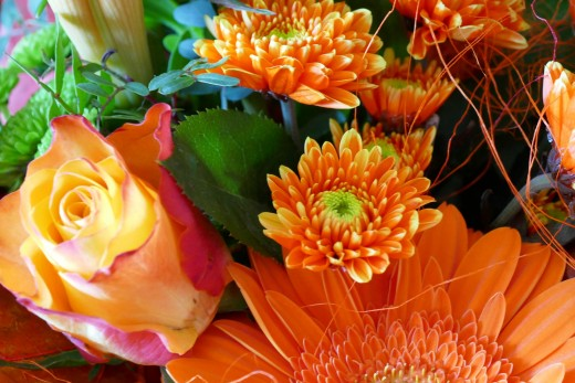 An autumn bouquet can be dressed up with candy, floral picks, and ribbon. For a spooky effect, attach fake spider webs and plastic bugs to an arrangement of dark blue and deep purple flowers.