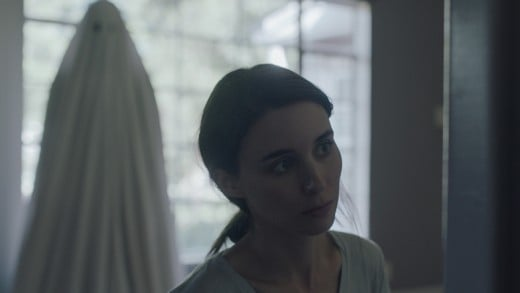 Rooney Mara ('M') with 'C' (Casey Affleck) watching her in the background.