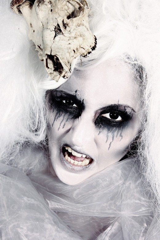 A base of white makeup with eyes emphasized with black eyebrow pencil or Halloween black from a kit.