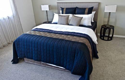 A typical double bed in a bedroom with the walls and floor carpet in an off-white colour. The bed had a dark blue trim.