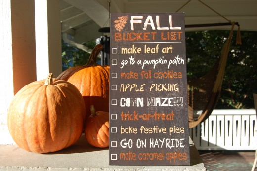 Fall sign with pumpkins on the front porch.