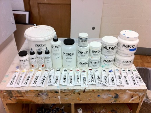 A photo of some of Golden Artist Colors line of acrylic paints, mediums, additives, grounds, and varnishes available today.