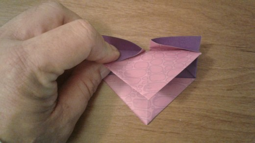 grab the top and fold it down towards the bottom triangle but don't crease it