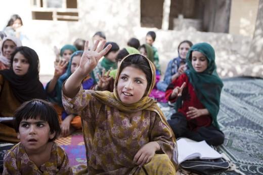 Khalida raises her hand to anwer a question in the Puti Kalatsha community-based education class