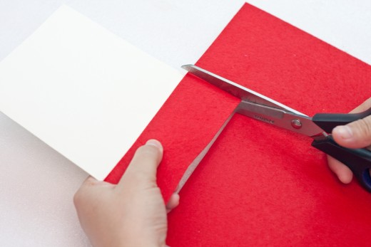 """Cut a piece of red felt or craft foam so it is the same width as the front of your card.  This piece should be about 1.5"""" to 2"""" wide."""