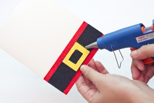 Glue the yellow felt/foam buckle onto the center of your black strip.  Cut a small rectangle of black foam or felt to the center of the yellow belt buckle and glue it into the middle of the yellow.