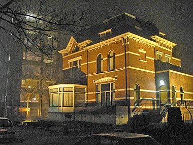 An office building is illuminated by high pressure sodium (HPS) lamps shining upward, of which much light goes into the sky and neighboring apartment blocks and causes light pollution.