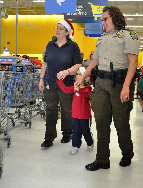 Pulaski County 'Shop with a Cop' director, reserve deputy sheriff Gwen Andrew Cavage (right) walks with Emma Roberts, and a Saint Robert Walmart employee, to their shopping cart, Dec. 21, 2013.