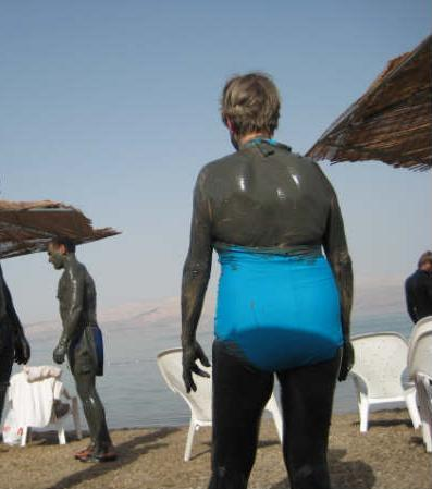 People covered in drying mud, on the beach by the shoreline of the Dead Sea, Israel. (c) this writer