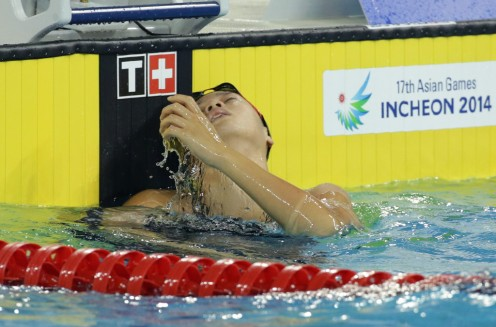 Swimmer Miki Uchida reacts after the women's 50 meter freestyle event during the 2014 Asian Games in Seoul, South Korea. She looks exhausted.