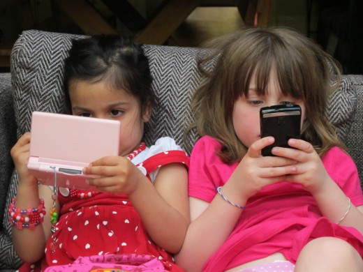 Two children. One playing with a DS. Other playing or chating on her phone. By Tony McNeill, 2011