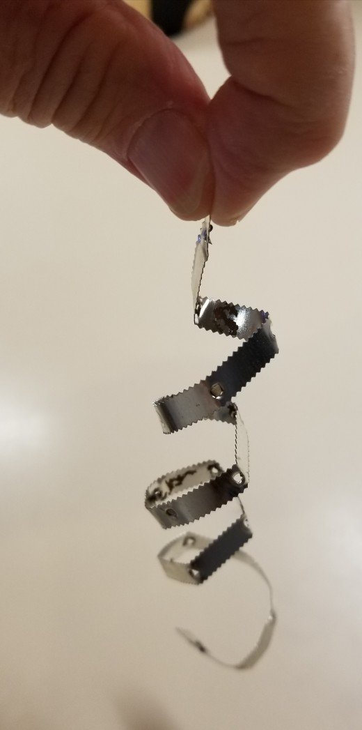 This spiral needs no cutting. It's the tear-off strip from a box of aluminum foil. You can shape it into this twirl by wrapping it around a pencil or around your finger.