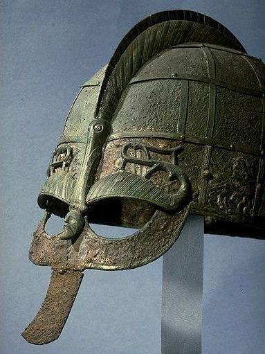 This is the distinctly Norse/Danish/Svear spectacled visor helm with decorative 'brow' over the visor and serpent head ridge to deflect blows to the head. Compare this with the...