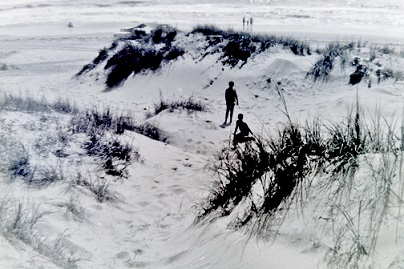 My brothers playing in the Padre Island sand dunes with Gulf waters in background.