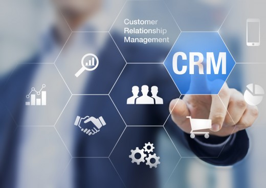 Customer relationship management concept with a businessman touching CRM button.