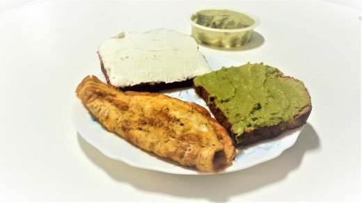 An omelet, whole wheat bread, white cheese and avocado spread