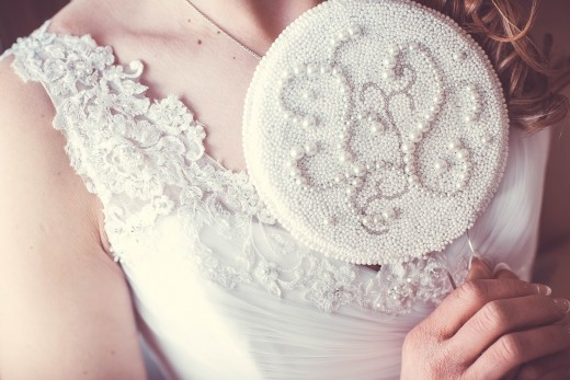 A wedding gown of beading in the scalloped lace neckline of a wedding gown. A gift of a beaded mirror.