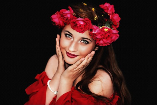 A garland of red flowers adorn the head of a woman with long brunette tresses.