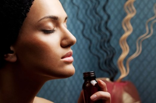 Woman breathes in essential oil to relax.