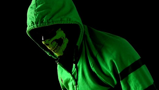 A green hooded costume covers the face of a human being with skull painted makeup.