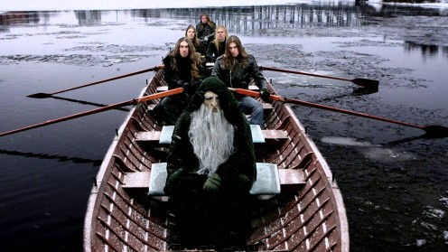 This photo shows the band members of Kalmah sitting in a big boat as they try to row through a lake. Sitting in the front of the boat is a very wise man.
