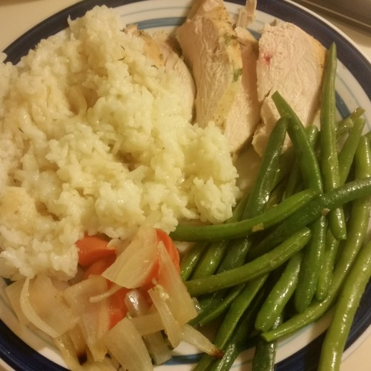 A full plate served up with lemon chicken, flavored rice, green beans with shallots and garlic, and lemon soaked carrots and onions.