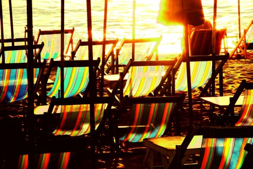 Beach deckchairs are silent witnesses of the sun and wind's competition.