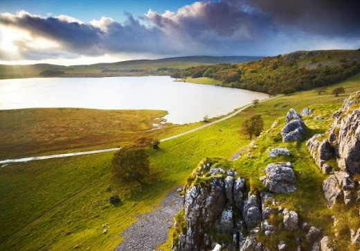 A favoured spot for anglers, Malham Tarn sits atop the moor, above the limestone pavement  - seen here with lengthening evening shadows