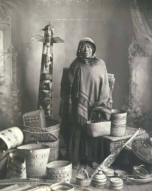 Salishan Indian woman with basket and native art collection.