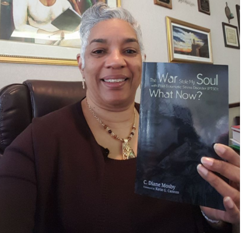 Rev. Dr. C. Diane Mosby holds book about her son's PTSD.