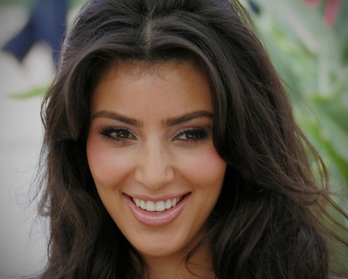 Kim Kardashian smiles and gives eye contact.