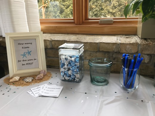 "Make sure you count the kisses! Kisses come in many colors so it's easy to carry on the color scheme. Have a jar for the guests to place their guesses and plenty of pens! Notice the framed ""name of the game"" sitting on sand and shells"