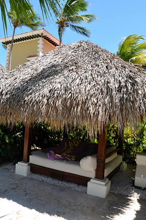 A thatched palapa adds an authentic touch to a tropical backyard.