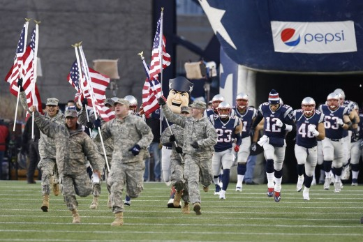 Members of the US Military run onto the field with the New England Patriots