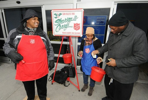 As Union College student Chris Brown and Sandya Sainvil ring bells for the Salvation Army kettle drive in 014 Al Williams drops a few dollars in while shopping Wal-Mart in Glenville on a Monday afternoon.