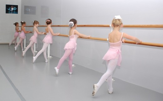 Young ballerinas practicing at the barre. Think about this scene from the viewpoint of the photographer. Then put yourself in the shoes of one of the children. How do they differ?
