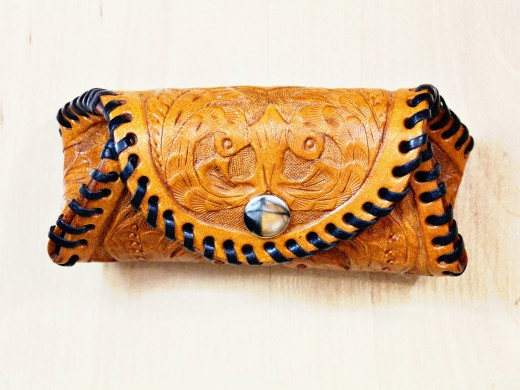 The completed hand carved leather coin purse with its ornate design.